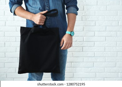 Young man holding textile bag against brick wall, closeup.  Mockup for design