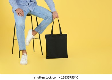 Young man holding textile bag on color background, closeup. Mockup for design