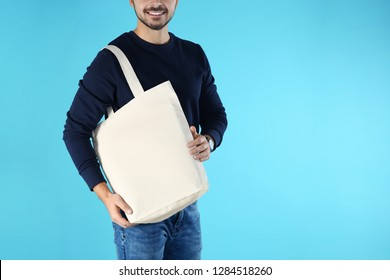 Young man holding textile bag on color background, closeup. Mockup for design