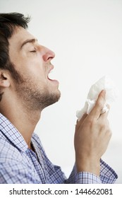 Young man holding tissue paper about to sneeze over white background