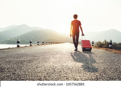 Young man holding travel bag walking on the roadway, summer nature outdoor.