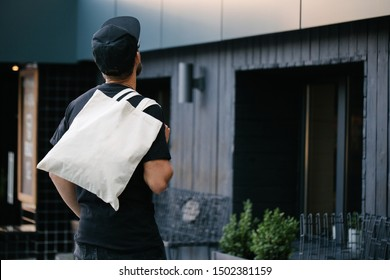 Young man holding white textile eco bag against urban city background. Ecology or environment protection concept. White eco bag for mock up.