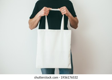 Young man is holding white textile eco bag on white background. Mockup for design