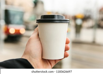 A young man holds a disposable glass with coffee or another hot drink in the cold season. Blurred street in the background.