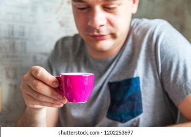The young man holds an espresso cup of coffee in hand. Focus on a cup