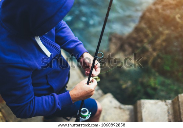 young man holds a fishing rod, catches fish in the nature on a sea background, hipster fisherman spends vacation on the blue ocean, active travel hobby fishing, rural outdoor sport tourism, top view