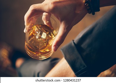 A young man holds a glass of whiskey with ice in an elegant scene 2