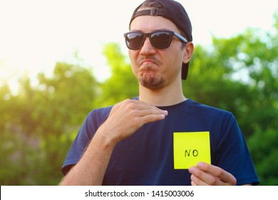 A young man holds in his hand a sticker that says no on a blurred background. Lifestyle portrait, toned. Emotion of categorical failure
