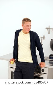 A young man holds a juicy green apple whilst standing in a kitchen environment.