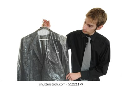 Young man holds newly dry cleaned business jacket coat