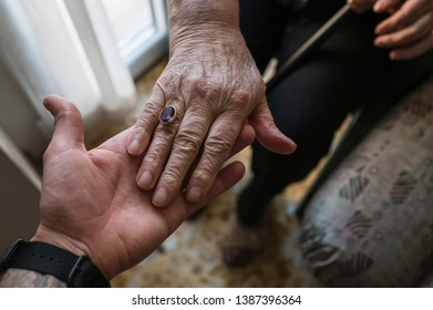 Young man holds a senior woman hand at home