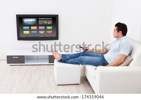 Young Man At Home Applying Setting Of Television Sitting On Couch