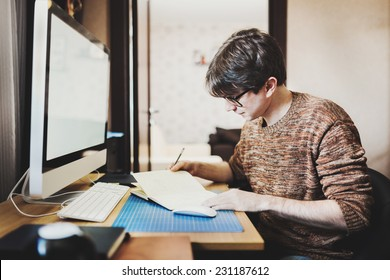 Young man at home using a computer, freelance developer or designer working at home