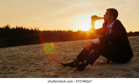 A young man in a hood finishes the last sip of beer from the bottle and throws the bottle. Sitting at sunset