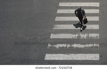 Young man in the hood is walking across the crosswalk at the junction street of city, Pedestrian safety, Aerial view