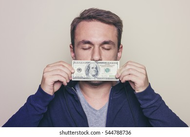 Young man in hoodie with a hundred dollar bill covering his mouth.