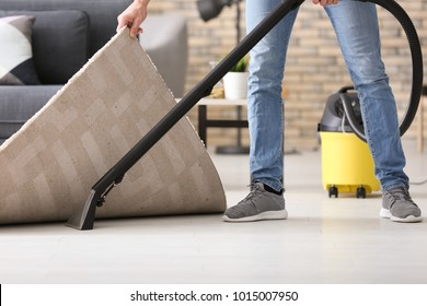 Young man hoovering floor while cleaning flat, closeup