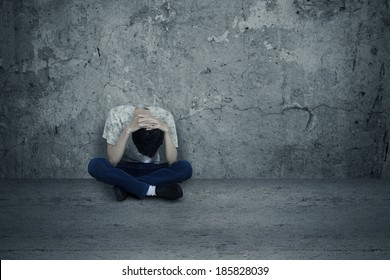 Young man hopeless sitting alone on the floor