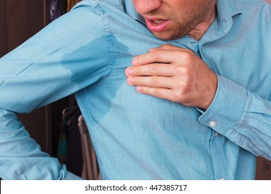 Young man in horror looking at the sweaty shirt