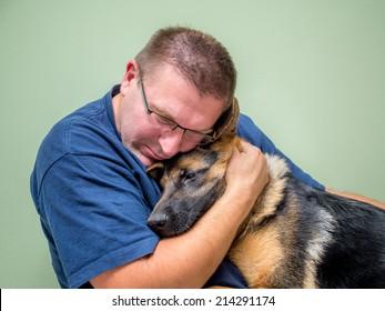 Junger Mann umarmt und tröstet seinen Hund