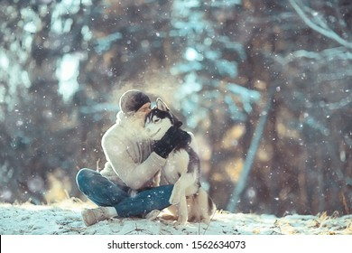 young man hugs a husky dog in the winter in the forest, a man and a dog hug together and play in a winter nature landscape