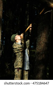 Young man hunting with a blowgun in summer forest