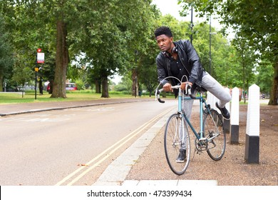 Young man in a hurry getting on his bike
