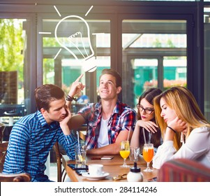 Young man with an idea, sitting with his friends in a cafe