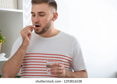 Young man ill with flu taking medicine at home