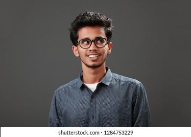 Young man of Indian origin looks sideways