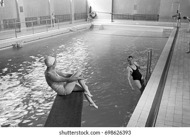 Young man in indoor swimming pool looking at woman sitting on diving board