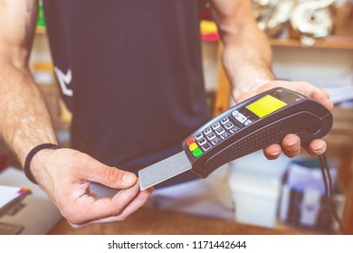 young man indoor using credit card reader paying bill with credit card - buying, paying, customer concept
