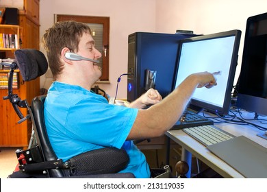 A young man with infantile cerebral palsy caused by a complicated birth sitting in a multifunctional wheelchair using a computer with a wireless headset reaching out to touch the touch screen