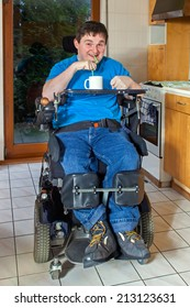 A young man with infantile cerebral palsy caused by complications at birth sitting in a multifunctional wheelchair enjoying a mug of beverage drinking through a straw