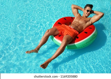 Young man with inflatable ring in pool on sunny day