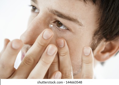 Young man inserting a contact lens isolated on white background
