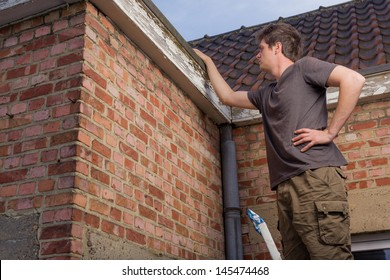 Young man inspecting the roof of an old house standing on a ladder