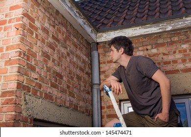 Young man inspecting the wall of an old house standing on a ladder