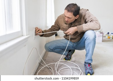 Young man installing television cable internet wire in room wall carpet floor flooring, white walls, during remodeling renovation, cleaning, inspection