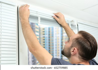 Young man installing window blinds at home