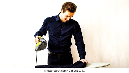 Young man ironing clothes on ironing board in home. Housework concept.