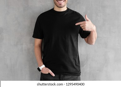 Young man isolated on gray textured wall, smiling while pointing with index finger to black t-shirt, copyspace for advertising
