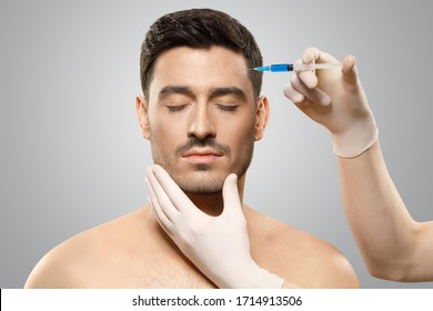 Young man isolated on gray background receiving botox injection from beauty doctor in sterile gloves in forehead to reduce aging, eyes closed