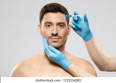 Young man isolated on gray background looking at camera while receiving botox into forehead to prevent sking aging by doctor in blue medical gloves. Face lifting male