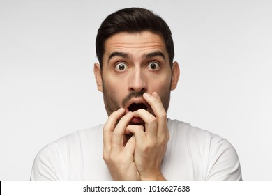Young man isolated on grey background dressed in casual clothes, covering mouth with hands and round eyes experiencing deep astonishment and fear