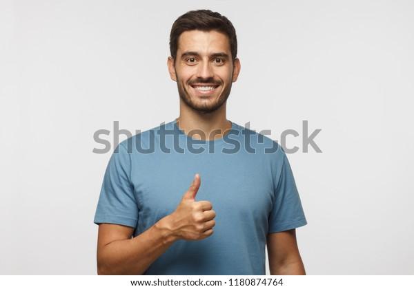 Joven aislado en un fondo gris que muestra el pulgar con emociones positivas y felicidad. Satisfacción con la calidad y la recomendación