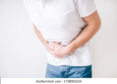 Young man isolated over white background. Cut view of guy holding hands over stomach because of diarrhea. Painful and aching.