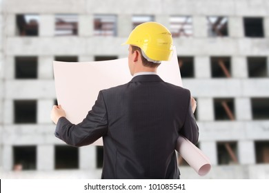 A young man in a jacket and a helmet on a construction site