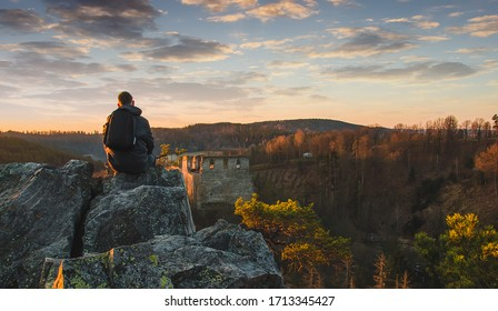 Young man in jacket, pants and backpack sitting and looking to ruin Divci kamen from rock. Czech republic - Shutterstock ID 1713345427