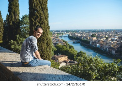young man in jeans enjyoing view on city and river in Italy